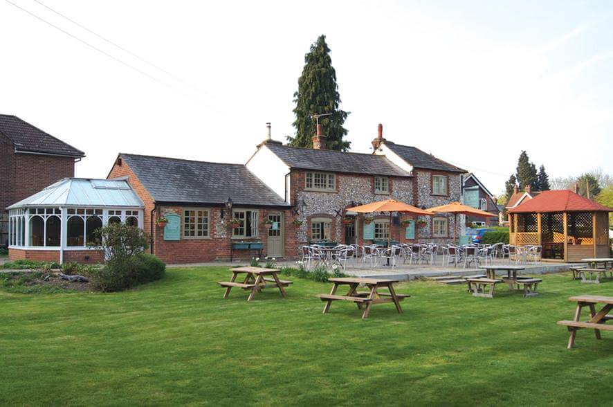rear of pub with a beer garden and tables